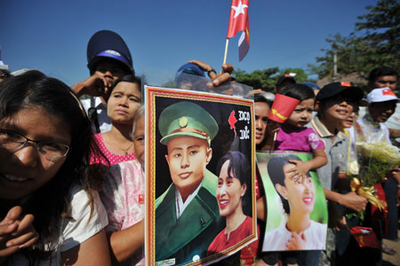 Supporters hold pictures of Aung San Suu Kyi and her father General Aung San