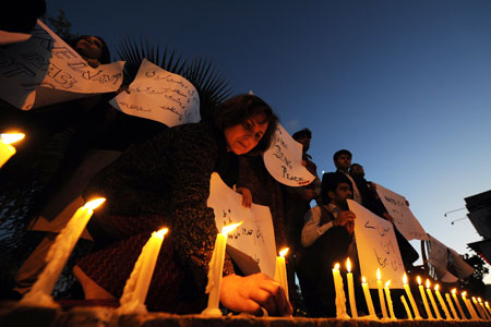Pakistani human rights activists light candles - to pay tribute to Pakistani soldiers killed in a NATO strike