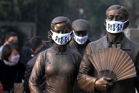 Wuhan pollution protests - statues wear masks with airborne particulate matter readings