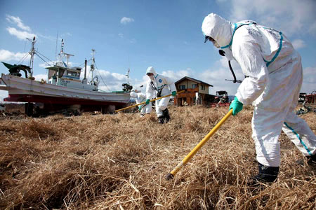 Fukushima radioactive leaks one year on - Japanese police officers search for missing persons in Ukedo