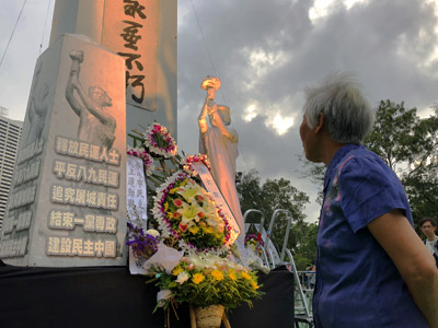 4 June 2018 rally: a lady pauses reverentially before a memorial at Victoria Park, Hong Kong
