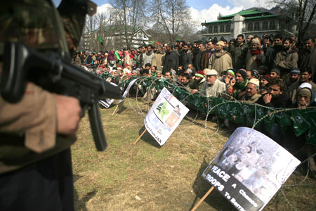 Kashmir flashpoint - Indian policeman stands guard at a PDP rally in Srinagar