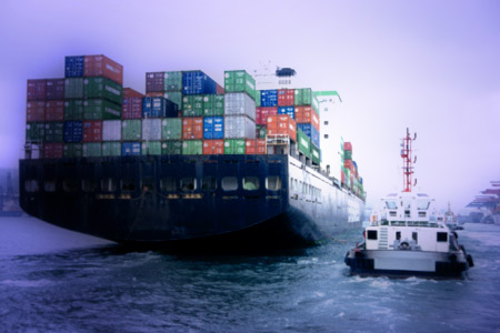 Container ship being escorted into Hong Kong by a tugboat