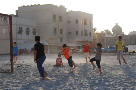 Football and politics in Middle East - kids play soccer in manama, bahrain sands